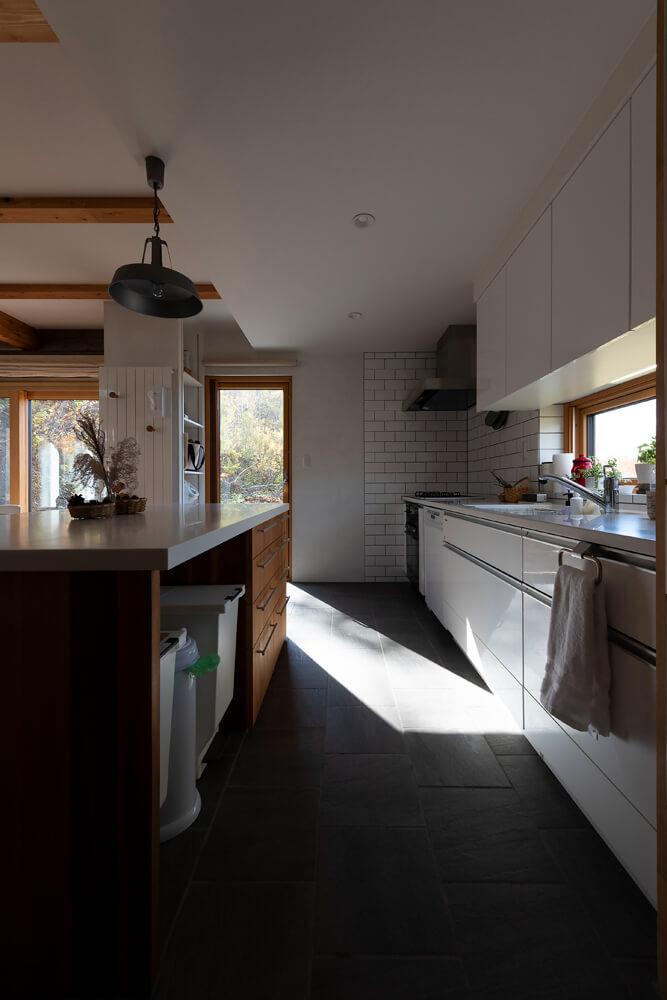 物をなるべく収納してすっきり見せているキッチン。アイランド部分とキッチン横の収納棚にゴミ箱や家電を集約させている