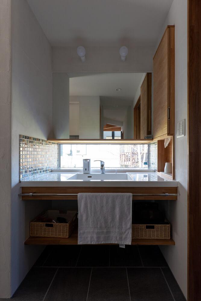 外光で手元が明るい洗面コーナー。収納棚には、電動歯ブラシを充電しながら収納できるなどうれしい工夫が施されている