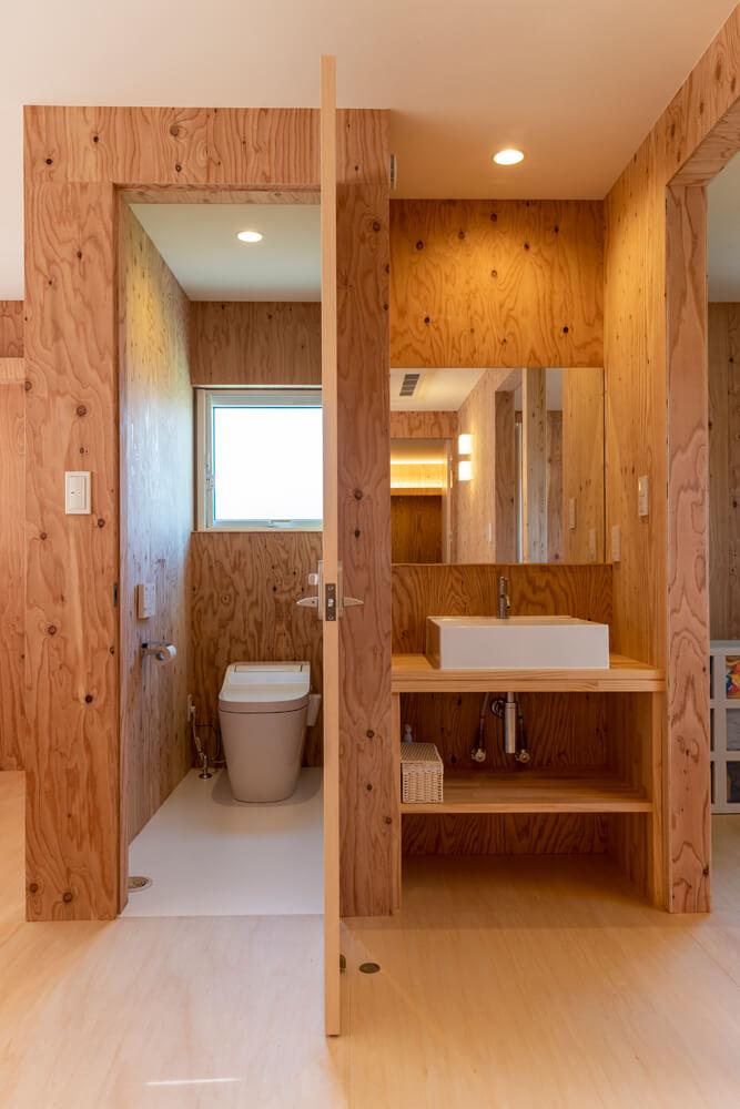 2階のトイレと手洗い。2階の壁にはすべて針葉樹合板を用いて、コストカットを図っている
