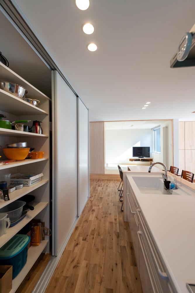 キッチン背面には、大容量の収納を完備。扉付きなので客が来た時などさっと隠せて便利