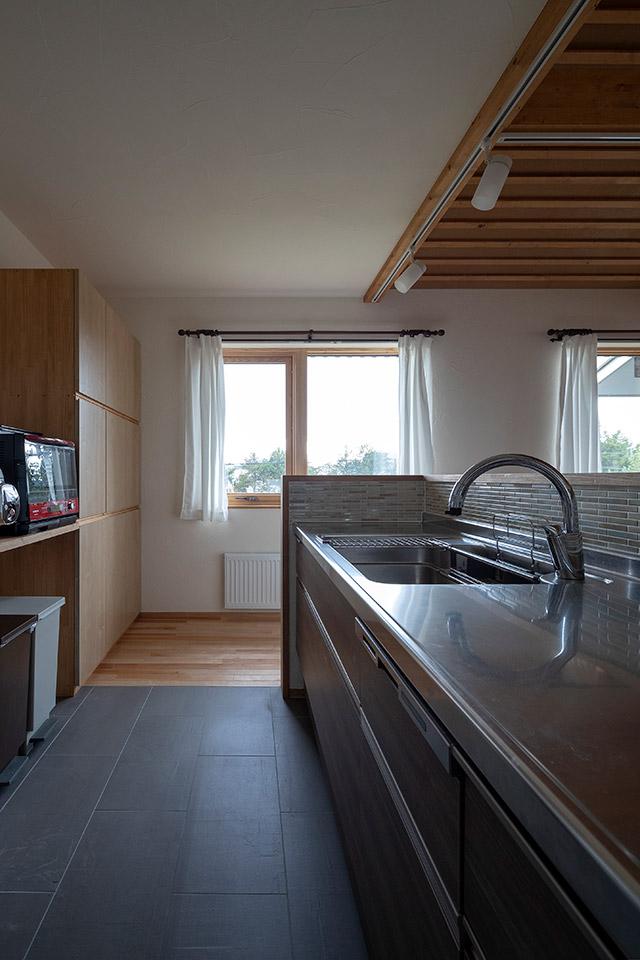 清掃性の高いスレート調のプレーンなタイルをキッチンの床に採用