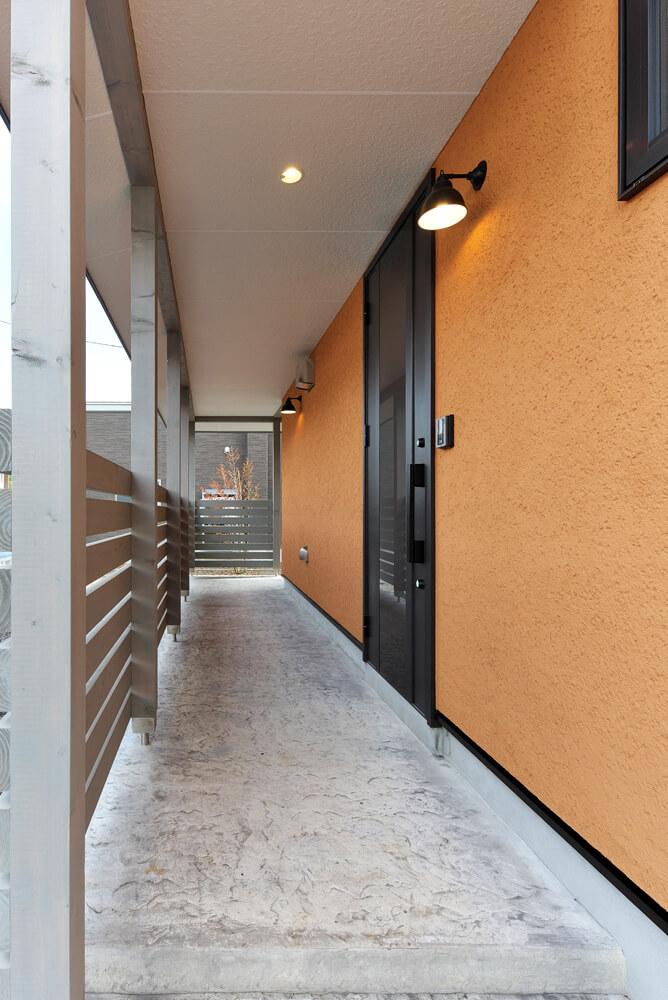 風除室の役割も果たす屋根付きのポーチ。床には表情豊かなデザインコンクリートを採用した