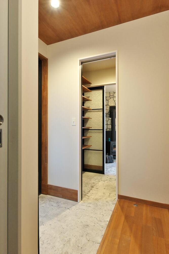 玄関からはシューズクロークを挟んで土間空間へとアクセス可。床はポーチと同じデザインコンクリート仕上げ