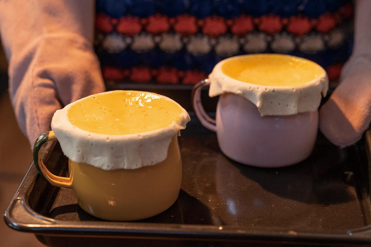 ホーローマグにシチューを入れて、パイ生地をかぶせ、卵黄を塗って炉内へ