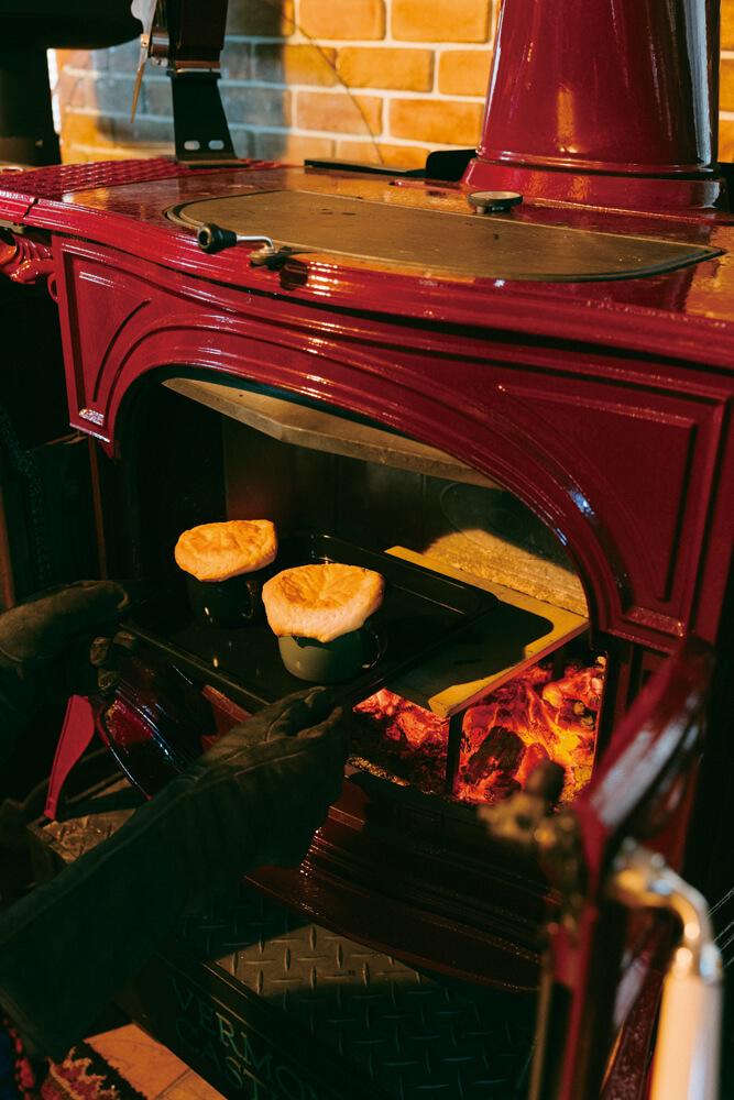 こんがり焼けたポットパイを炉内から取り出す