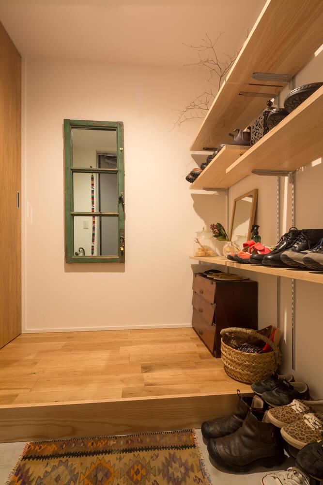 コンパクトながらも機能的で美しい玄関。下足入れはあえてつくらず、造作の可動棚で見せる収納に