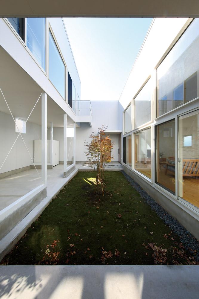 北側から中庭を見る。通風のためのピロティの開口部は、隣家の開口部との位置関係を計算して設けた。白いガルバリウム鋼板の外壁に中庭の植栽の彩が加わる