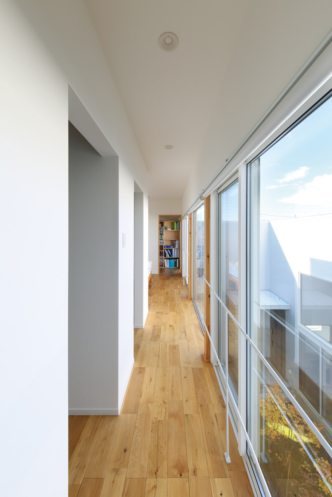2階の廊下。掃き出し窓の大きな開口部でLDKと中庭の様子が感じられる。奥にはNさんの隠れ家的書斎