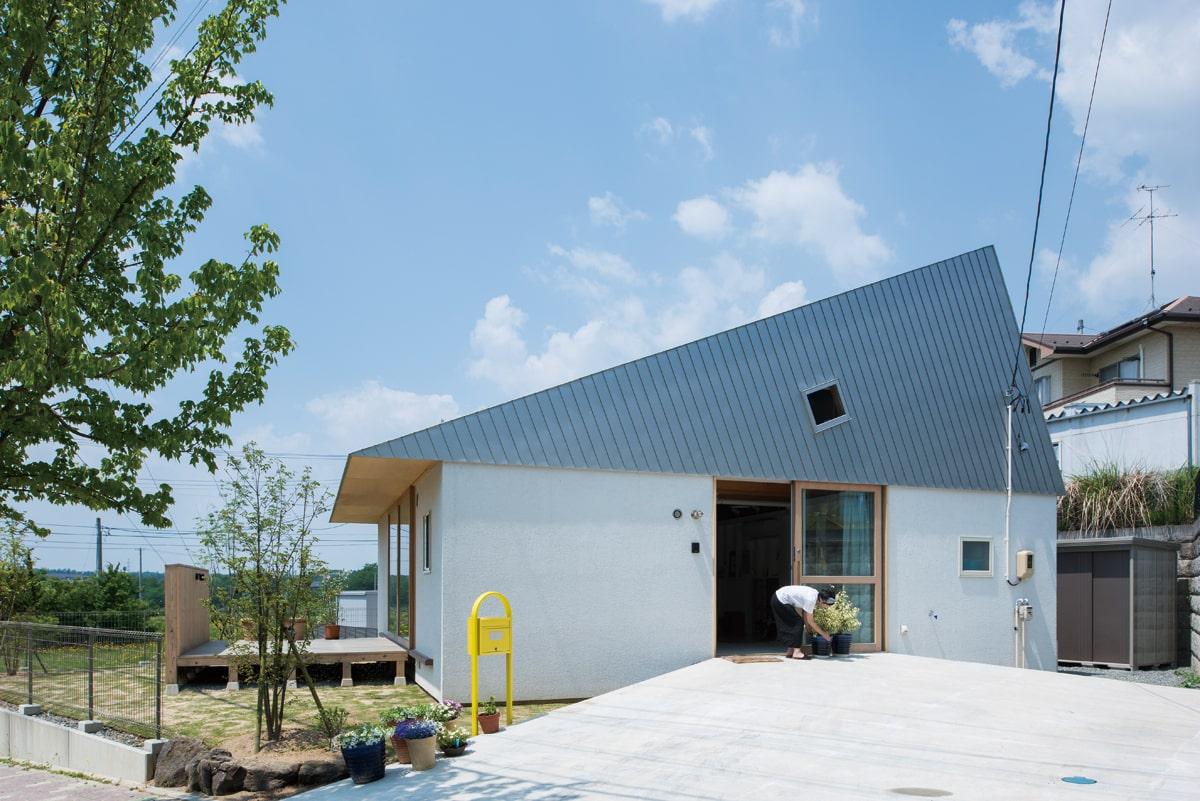 変形敷地に対して斜めに住宅を配置。四隅に生まれた場は駐車スペースや庭になっている。家だけでなく敷地全体で暮らしを設計した住まい