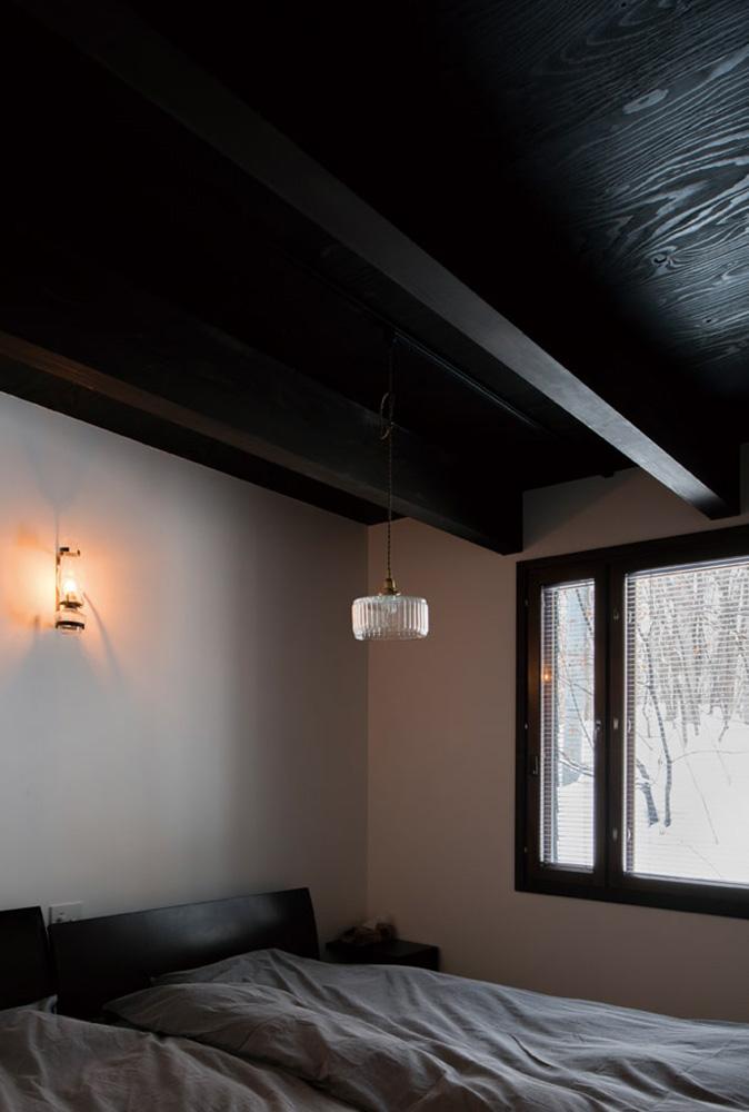主寝室の壁には、古いオイルランプをリメイクした壁付け照明をさりげなくレイアウト