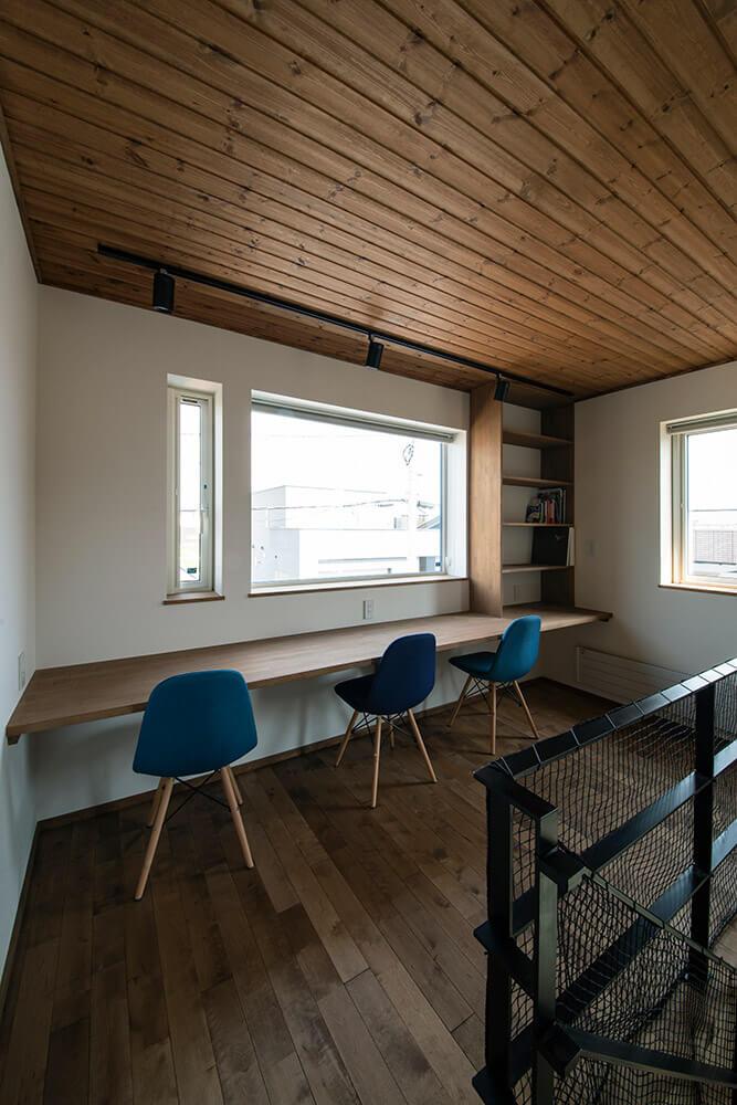 こちらは壁と窓に向かってつくられたワークスペース。3人でもゆったり座れる広々としたカウンターは、右端に本棚も造作し、家族みんなで使うことができる