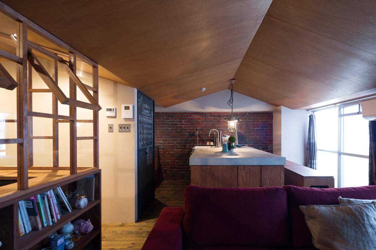 リビングからキッチンを見る。リノベーションによって屋根型の天井を得た空間が特徴的。正面の壁はモルタルをコテ仕上げによってレンガに見立てた技アリの職人仕事
