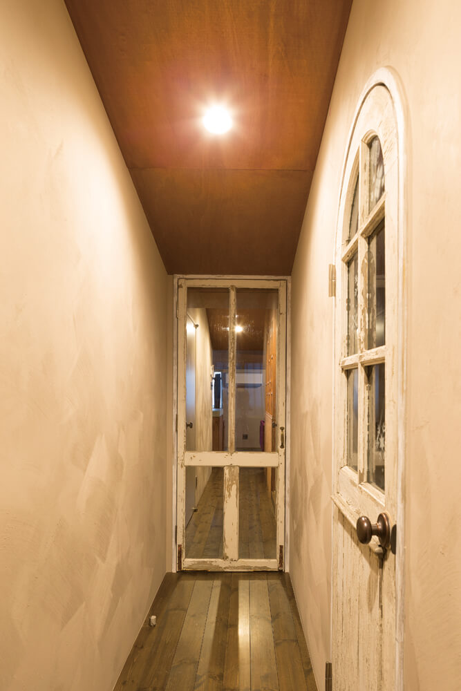 廊下からリビング方向を見る。ビンテージ加工を施した室内ドアやアンティークのドアノブに施主夫妻のこだわりが見て取れる