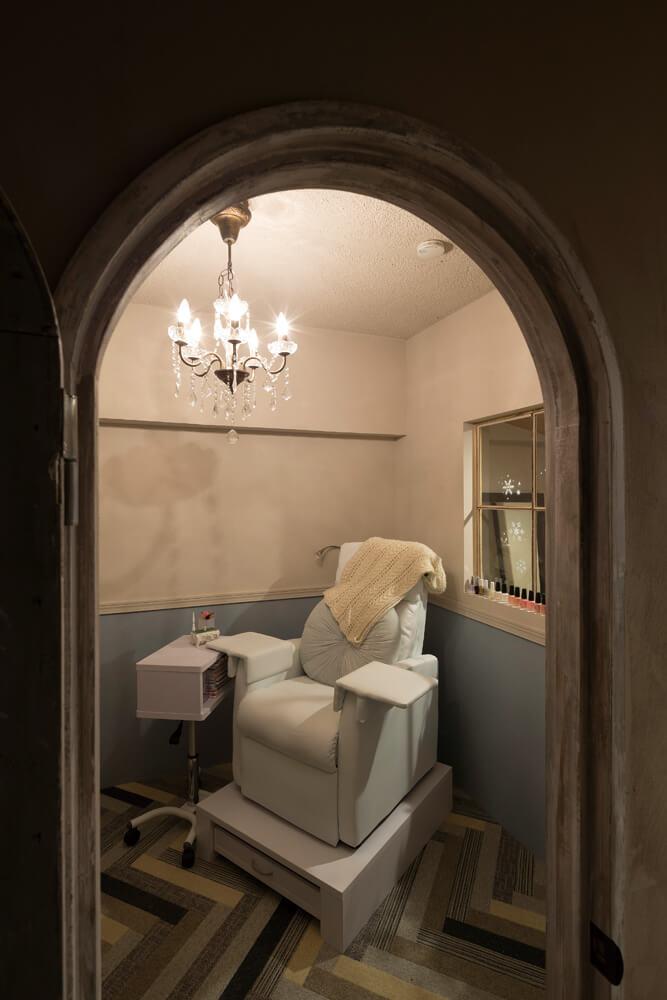 曲線を描くドアの向こうがネイルサロンスペース。ヘリボーン柄に張られた床材や小ぶりのシャンデリアにセンスを感じる