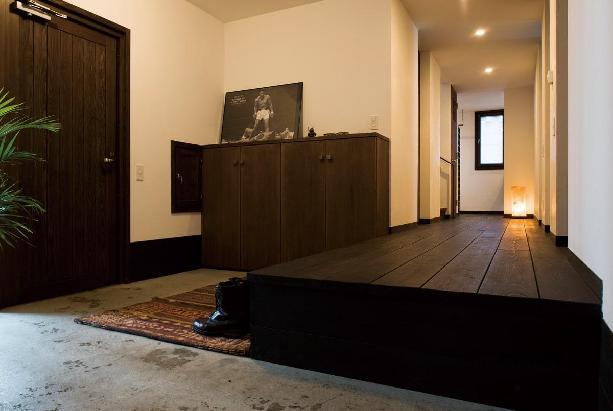 コンクリート土間を備えた玄関は、室内と車庫、それぞれにつながる動線を設けて