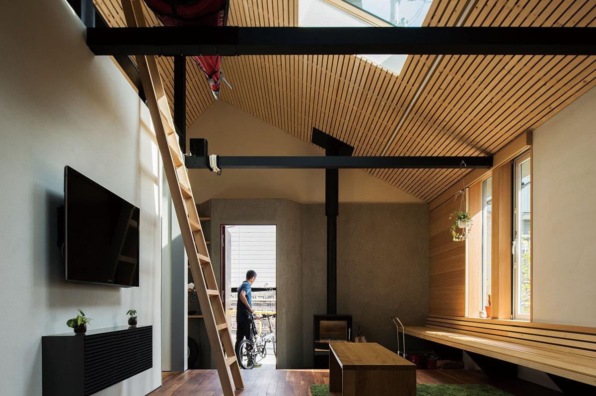三角屋根の形状を生かしたLDK空間。薪ストーブは玄関入ってすぐのところに置かれている