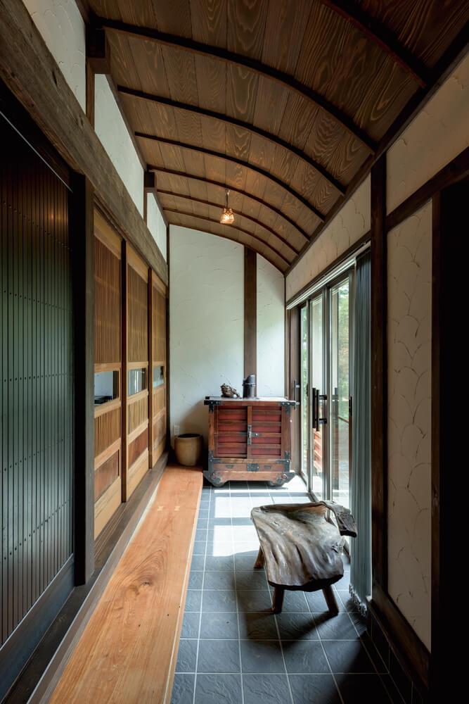 玄関土間に、旧宅の曲がり天井を活かした。古い欅の車箪笥が、空間に自然と馴染んでいる