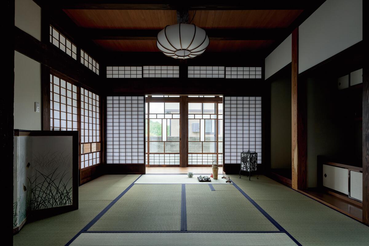 茶道を嗜む奥さんのために炉を切って設えた、上質感の漂う和室。広縁のガラス戸とも見事な調和を見せている。照明も古いものを再利用