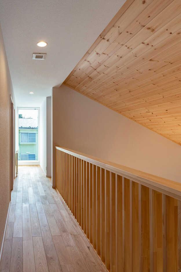 吹き抜けに面して廊下を設けた2階。傾斜天井はパイン材とすることでメリハリが生まれ、広がりも感じられる