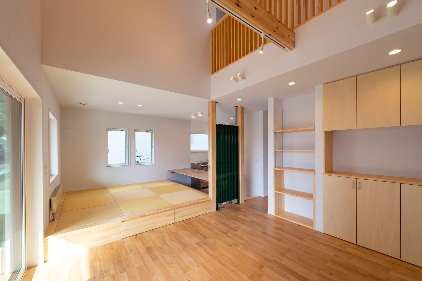パイン材とルナファーザーなどの素材感が際立つYさん宅のLDK。造作棚を設置するなど収納部分が多いのも特徴。小上がりとリビングの段差30㎝を生かして床下収納を設置した