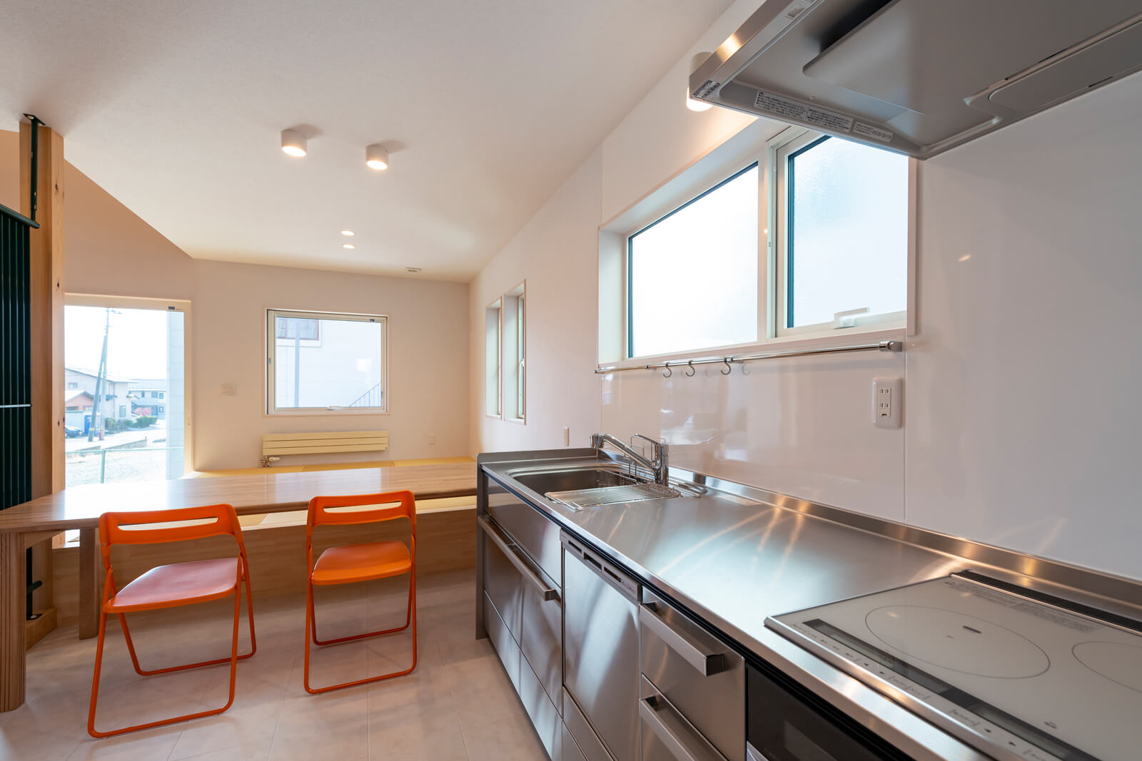 調理台のすぐ横にダイニングテーブルを設置。床をリビングより1段低くして、小上がりに腰掛けながら食事がとれるようになっている