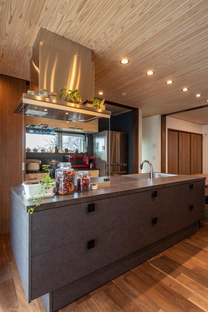 家づくりの核となったアイランドキッチン。このキッチンのサイズや雰囲気に合うよう間取りや内装をプランニングした。キッチン背部の収納スペースは4枚引き戸を閉じれば冷蔵庫まで隠れてスッキリ