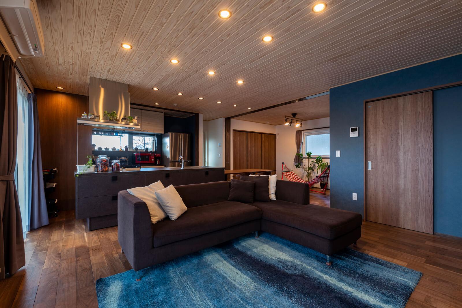 Fさんご家族の団らんの場にキッチンを据えたリビング・キッチンスタイル。板張り天井、ブラックウォールナットの床に、ブルーの壁がアクセント