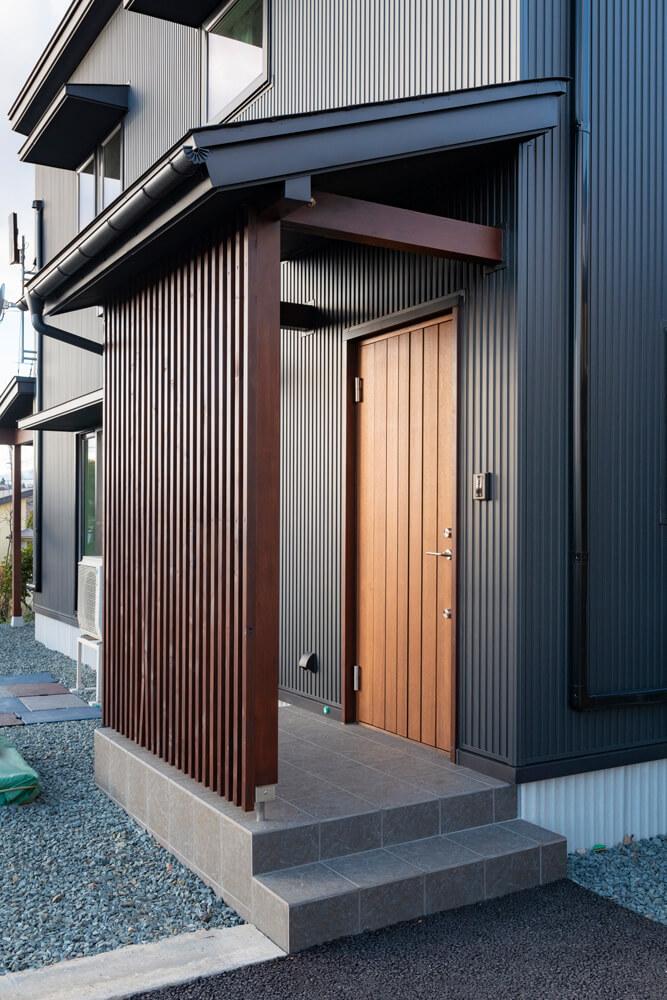 木製断熱ドアを採用した玄関。開口部は庇を出して日射の取得と遮蔽に配慮