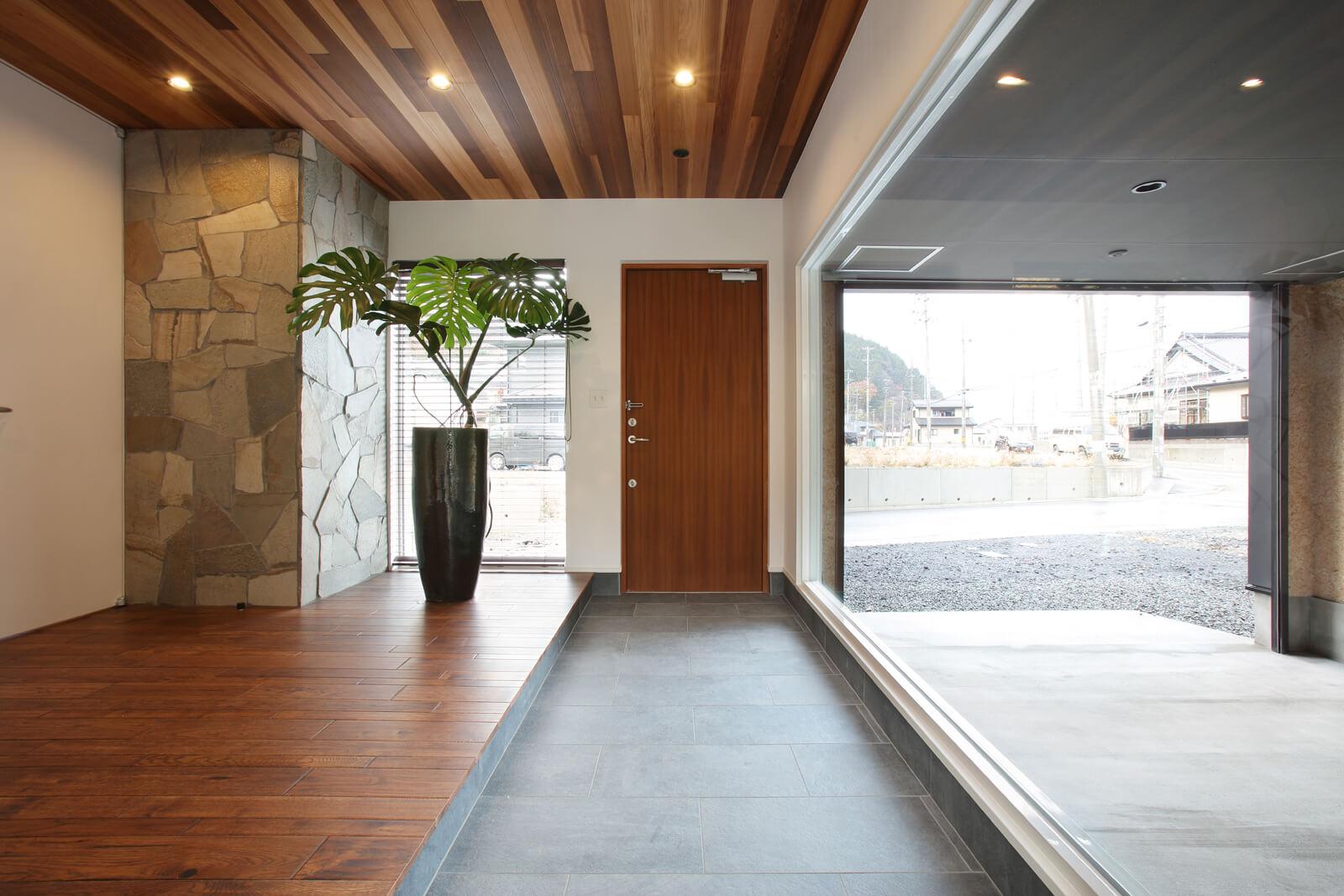 ゆったり広い玄関ホールは、この家の「顔」。特大サイズのガラス越しに愛車を眺めるダイナミックなプラン