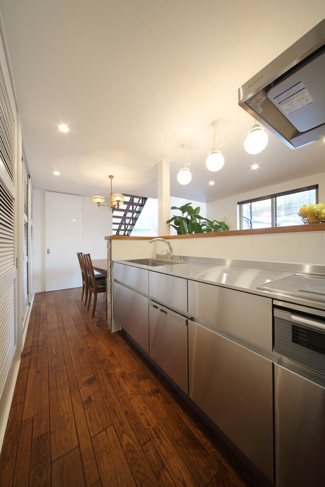 デザイン性と機能性を併せ持つオールステンレスのキッチン。背部には大容量の収納スペースも