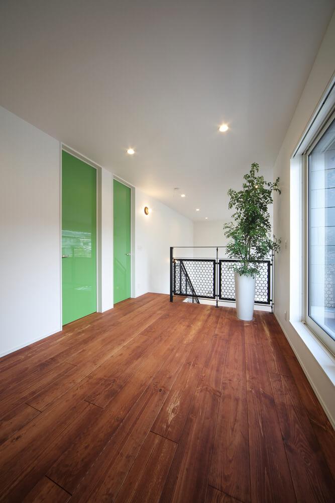 フレキシブルに使える2階ホール。各室の扉は色鮮やかなグリーンの鏡面仕上げ
