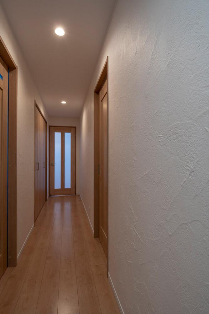 玄関から廊下にかけて、漆喰壁を採用。職人の熟練の技によるムラ感のある仕上げがアクセントに