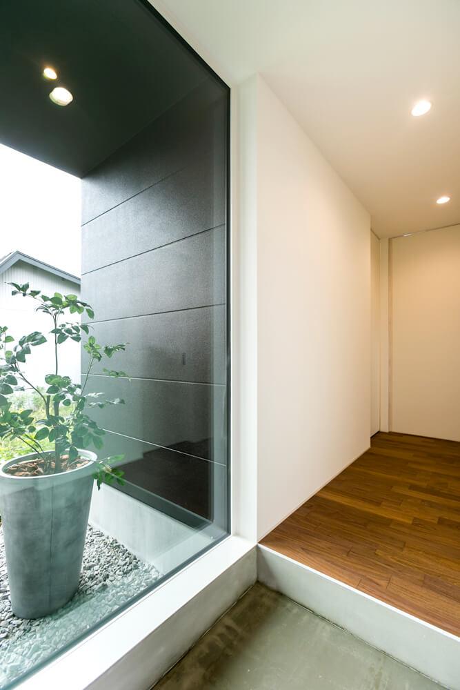玄関を入ると、左手のガラス越しに庭が広がる。廊下を進んでLDKへ