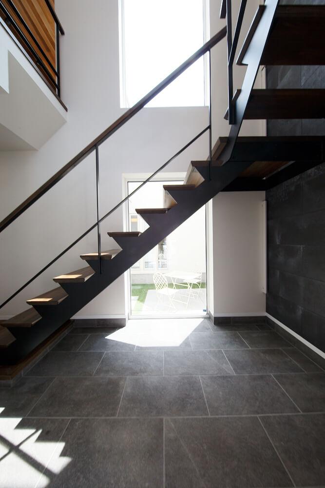 室内に入ると存在感のある階段が現れ、その向こうに中庭が。2つの窓からたっぷりと陽光が射し込む