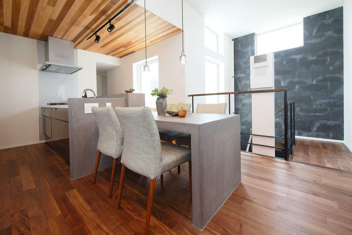 横並びで配置したダイニングとキッチンは、水に強くデザイン性も高いモールテックス仕上げ。正面の窓から中庭が望める