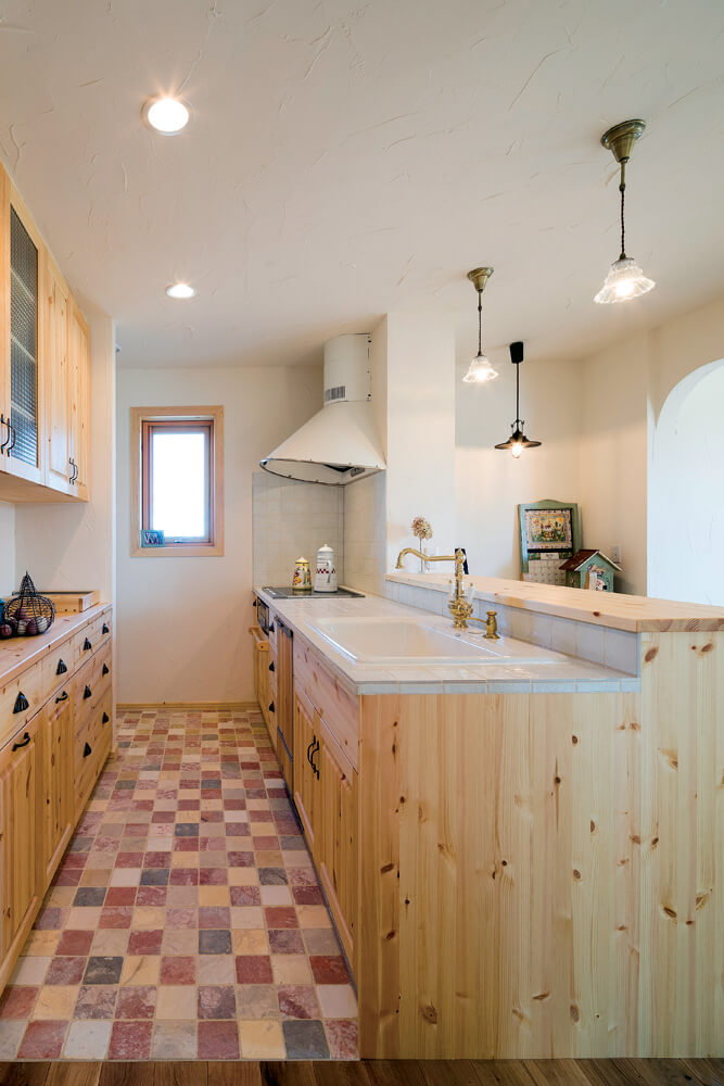 パイン材を用いた造作仕上げの対面式キッチン。背面収納から左に回り込むと、パントリーが設けられている