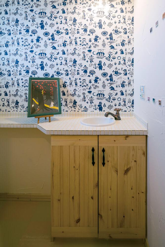 2階に設けられたトイレには、奥さんが大好きなムーミンをモチーフにした壁紙やタイルを採用。手洗いカウンターは造作