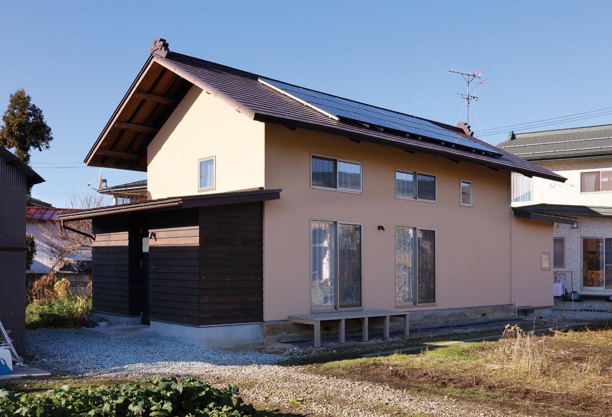 切妻屋根が印象的な外観。母屋側を背にして建つことで、適度にプライバシーを保っている。屋根には太陽光発電パネルも搭載