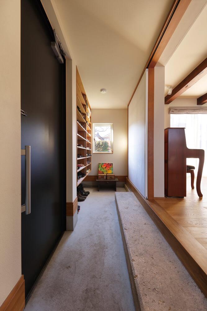 蔵の上がり框を、そのまま新たな家の玄関の上がり框に。玄関ドアの並びに下駄箱を造作した