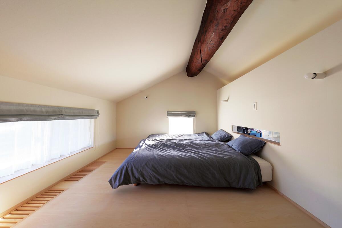 屋根なりの勾配天井の寝室は、屋根裏部屋のようにこもれてほっとできる空間