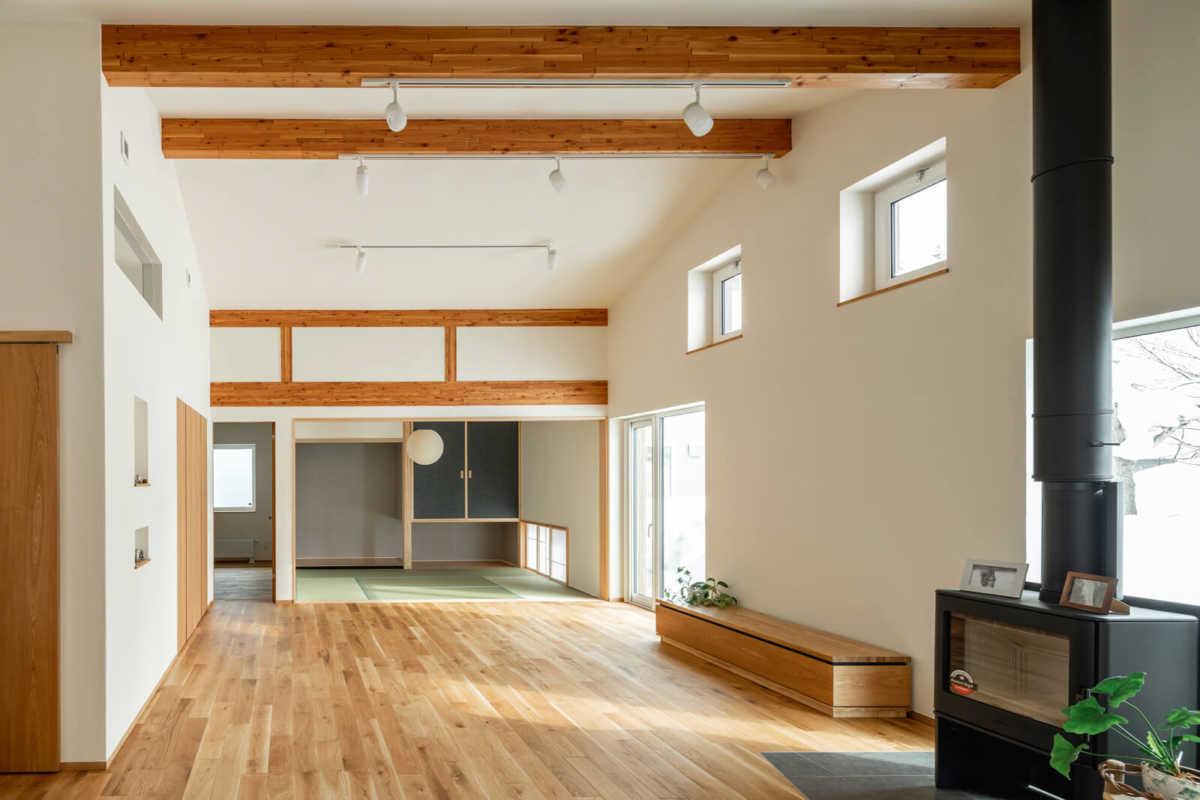 平屋ならではの天井の高いリビング。これだけの大空間をつくれるのも、躯体の耐久性が高いからこそ。奥に見える床の間もある本格的な和室には、吊り押し入れやサッシの内側に障子戸をつけ二重にした地窓も設けた