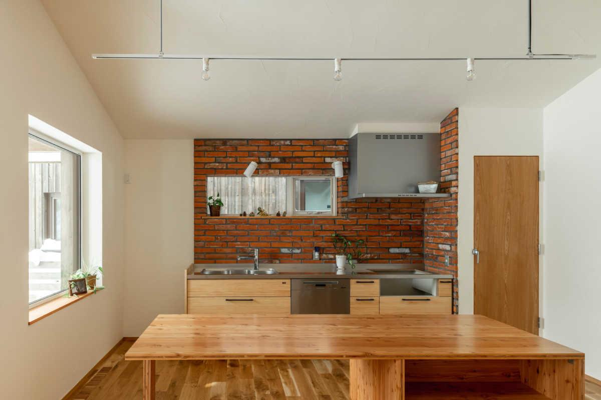 廊下を抜けて右側に配置されているキッチンは、壁向きでレンガをあしらい高級感がある雰囲気に。ダイニング兼作業テーブルが便利