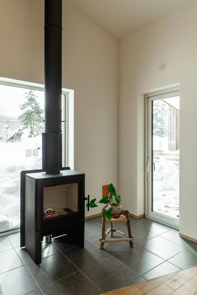 薪ストーブの炉台は石タイル敷きに。スタイリッシュなデザインのストーブに合わせた空間