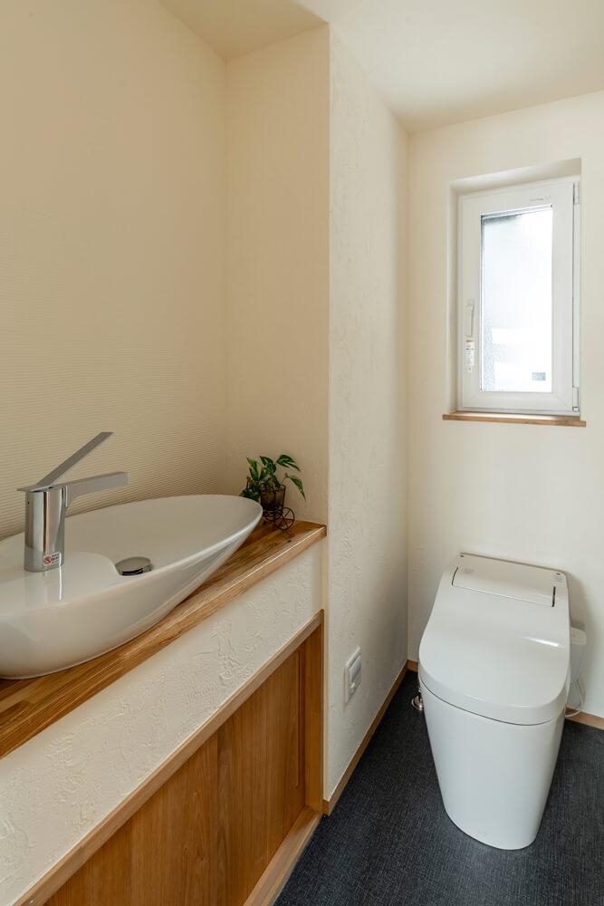 子ども部屋の手前に位置するトイレには、壁に組み込んだ収納と手洗い場を造作。上部分は空けて圧迫感がないよう工夫した