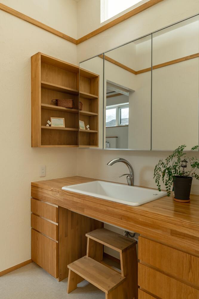 造作の洗面台と収納棚は使い勝手も抜群。上にはリビングにつながる採光窓
