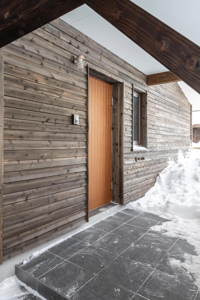 広い玄関ポーチは屋根付きで、雨や雪を気にせずカーポートへ行ける。外壁はオール木張り。天然成分の仕上げ剤を使っているので、自然な変化を楽しむことができる