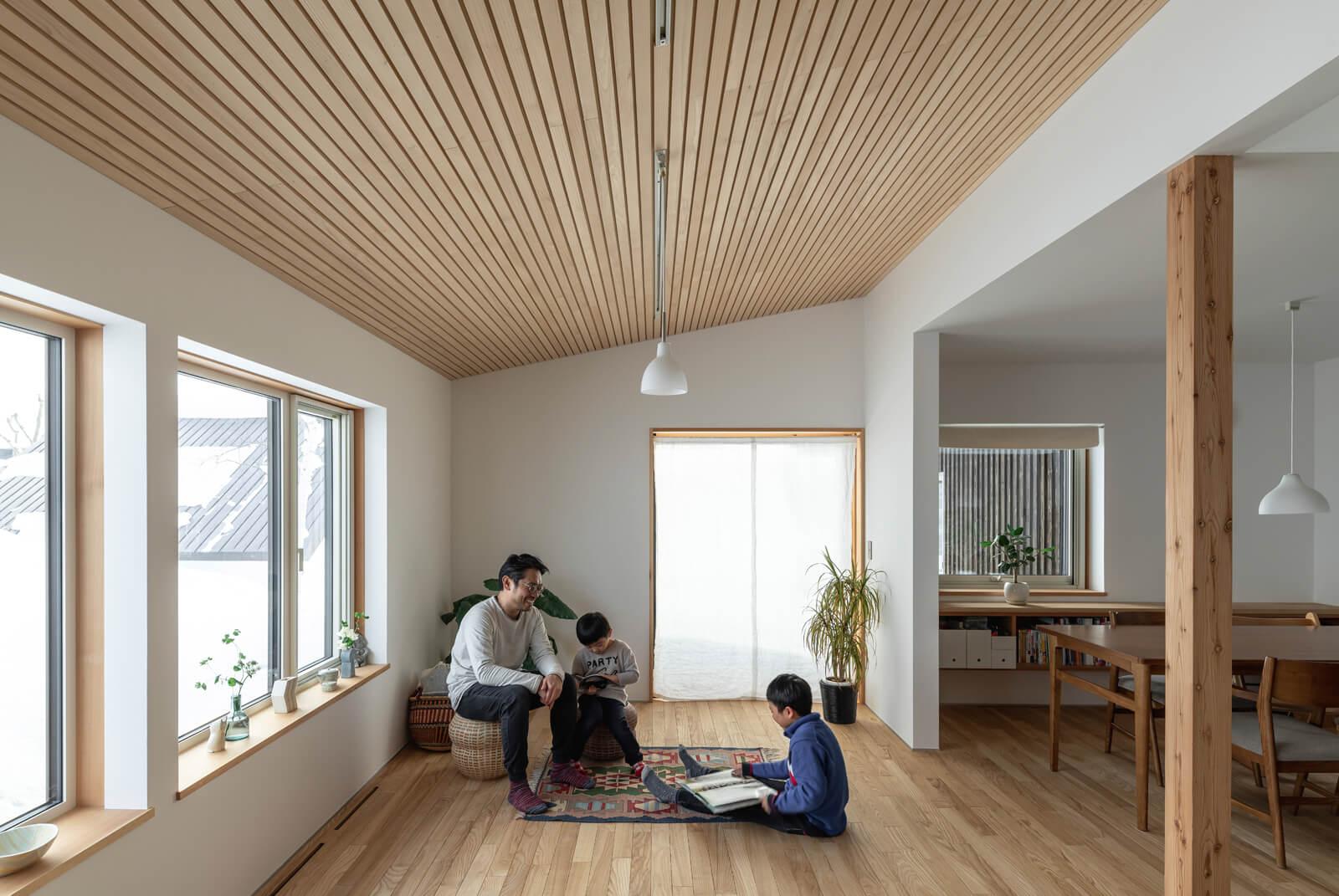 トドマツを張った屋根なり天井と大開口が面積以上の広がりを感じさせるリビング。リビングからダイニング、玄関ホールは間仕切りなしでそのままつながっている