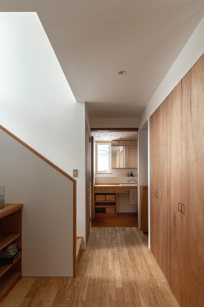 玄関ホールには水まわり、キッチンへつながる裏動線が設けられている。キッチン裏側にあたる壁には、パントリー的な役割を果たす造作収納を設置