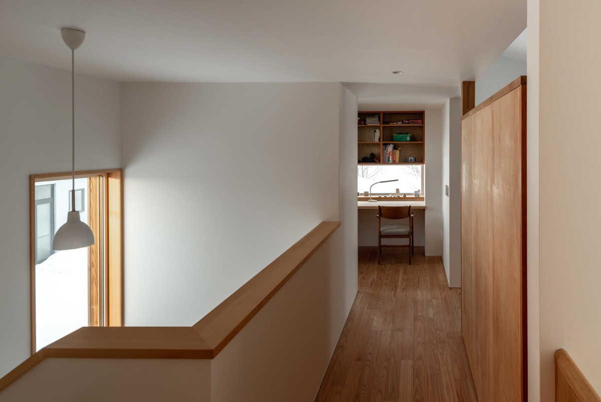 2階廊下と子ども室は、可動式造作収納で間仕切りしている。突き当たり奥は、Oさんの書斎。床は足触りがやさしいカラマツ無垢材を採用