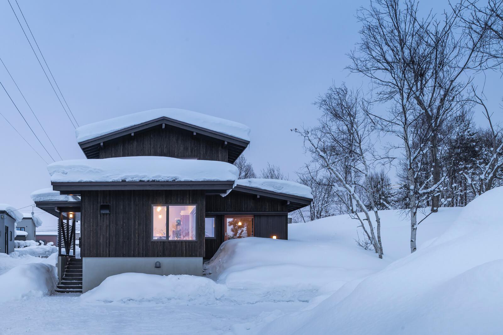 雪景色に映えるカラマツ板張りの外観。手前は奥さんの陶芸アトリエ